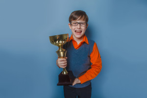 European-looking  boy of  ten years  in glasses holding a cup, award joy on a blue background