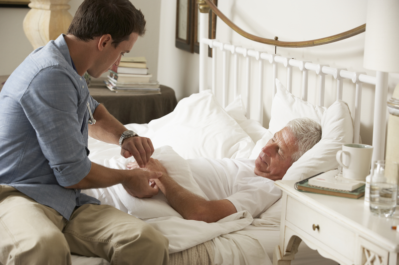 Doctor Taking Pulse Of Senior Male Patient In Bed At Home
