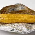 yellow corn baked in foil on a white table