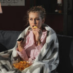 Beautiful young woman eating unhealthy food while watching TV at night