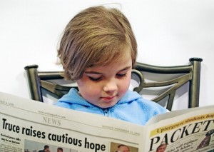 child reading paper