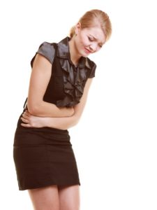 Bellyache, indigestion or menstruation. Young woman girl suffering from stomach pain isolated on white.