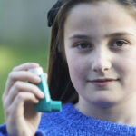 Girl Using Inhaler To Treat Asthma Attack