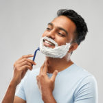 indian man shaving beard with razor blade
