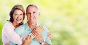 Happy senior loving couple over green nature background