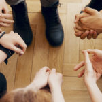 High angle view of hands of people in group therapy, talking and supporting each other