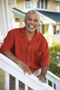 African American middle aged man smiling at viewer and leaning on stairway railing.